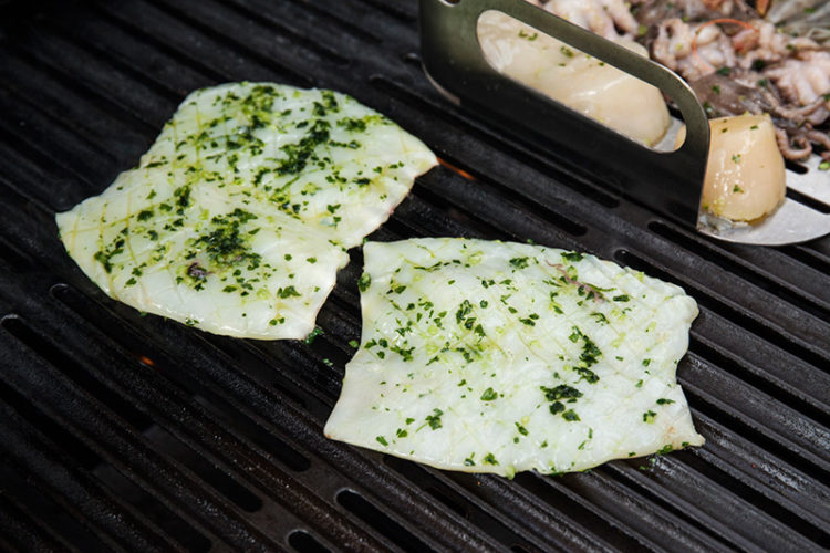 For the calamari, slice the tube open, flatten and score gently on one side into a checker board pattern. Place the calamari directly on the grill with the checker board facing up and begin to grill.